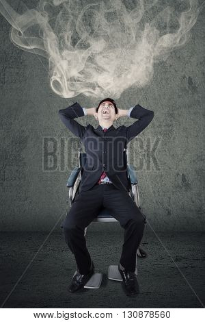 Portrait of stressful handicapped businessman sitting on the wheelchair with smoke in his head