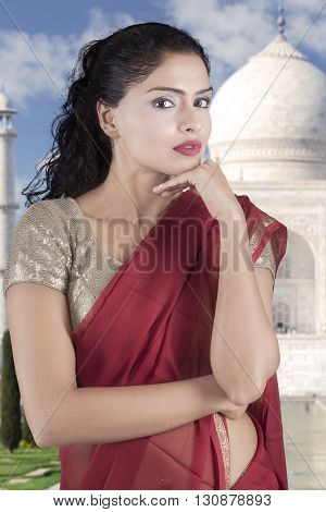 Beautiful Indian woman wearing a red saree clothes and looking at the camera with Taj Mahal background
