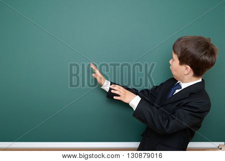 school boy in black suit show on chalkboard and wonder, point on blackboard background, education concept