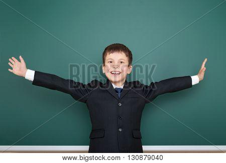 school boy in black suit open arms on green chalkboard background, education concept