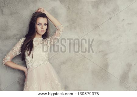 Gorgeous woman on a concrete wall background