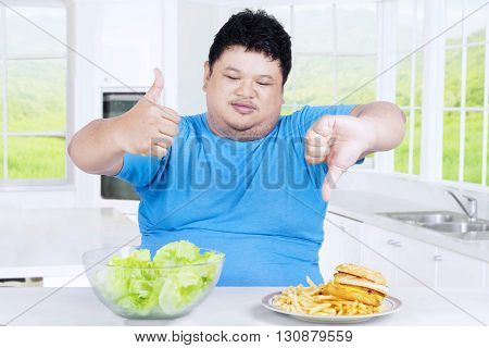 Picture of obesity person showing thumb up at the organic salad and thumb down at the hamburger