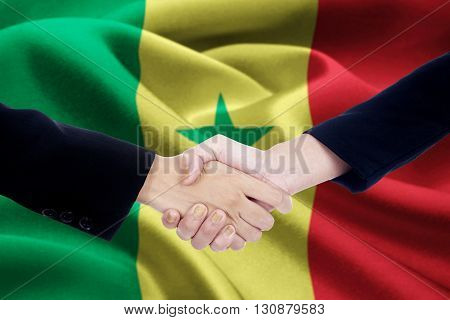 Photo of partnership handshake with two businesspeople hands closing a meeting and shaking hands with a Senegal flag background