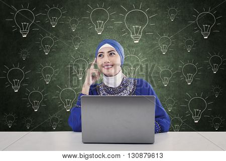 Pensive female muslimah sitting in class with hand drawn lightbulb