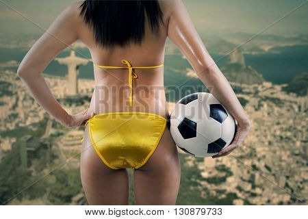 Woman's Sexy Backside Holding a Soccer Ball and looking at
