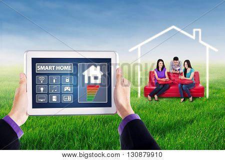Image of two hands holding smart house system controller on the tablet with group of young people using smartphone on the sofa at field