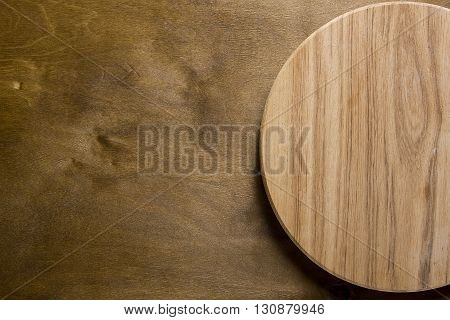 Empty cutting board on a brown wooden background