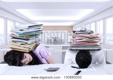 Portrait of two exhausted businesspeople sleeping in the office with a pile of paperwork on their head