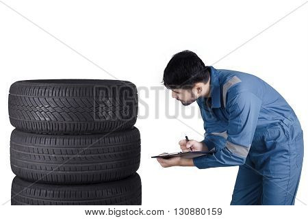 Picture of a young Arabian mechanic checks the tires while writing on the clipboard isolated on white background