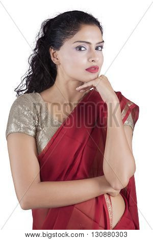 Pretty Indian female model looking at the camera while posing and wearing a red saree clothes in the studio