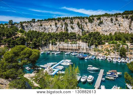Graceful sailing yachts in the deep sea gulf. The picturesque fjord with turquoise water at coast of the Mediterranean Sea. National park of Calanques in Provence, between Marseille and Kassis