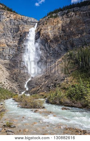 Rocky Mountains of Canada. Yoho National Park. Autumn waterfall forms full-flowing water flow of pearl color