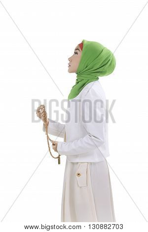 Young muslim woman holding prayer beads isolated over white background