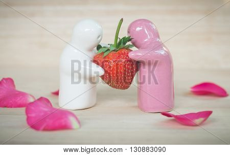 Ceramic toys giving a strawberry to couple for their love romantic background (vintage effect)