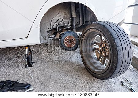 Car mechanic changing tire, changing tire with wheel wrench.