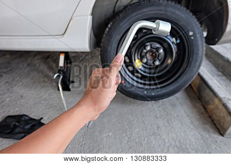 Car wheel changed by Wrench. changing tire.
