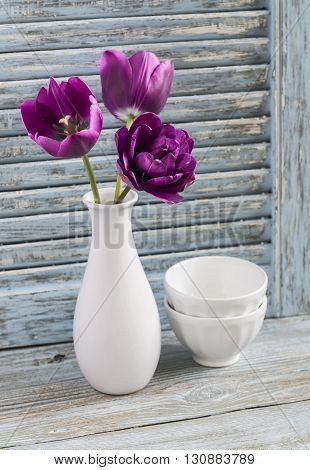 Purple tulips in a ceramic vase and white ceramic bowl on a blue wooden background. Still life in vintage and rustic style