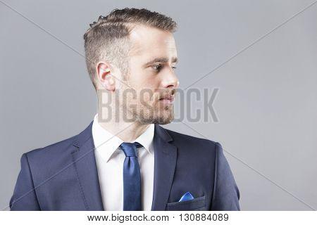 Confident business man looking forward against grey background