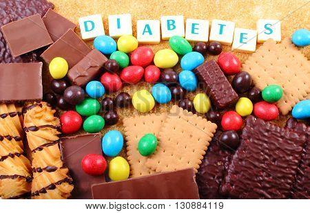 Heap of sweet candies and cookies with brown cane sugar and word diabetes unhealthy food concept of diabetes and reduction of eating sweets