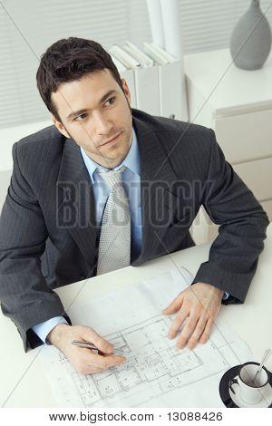 Junger Geschäftsmann, sitzen am Schreibtisch, Büroplan Planung. Obenliegende Schuss.