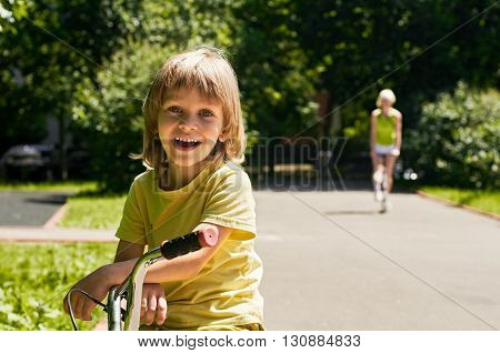 boy with bike portrait and mother with scooter on background