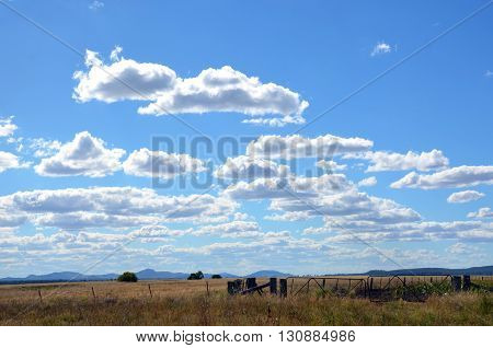 Fence line and gates on farmland under blue skies