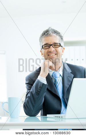 Businessman with grey hair, wearing grey suit and glasses thinking over laptop computer, sitting at office desk leaning on hand, smiling.