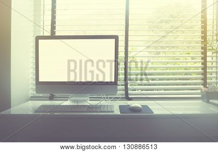 computer on white desk beside window soft style with vintage filter effect.