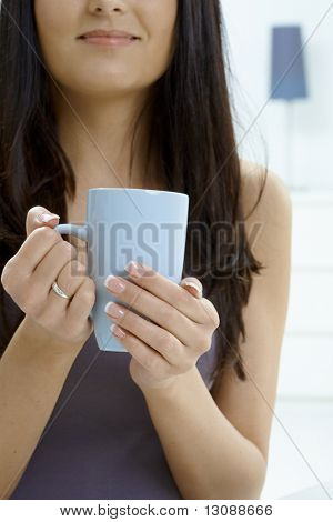 Partially visible young woman holding tea cup. Selective focus on hands.