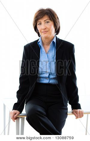 Studio portrait of senior businesswoman in black suit and blue shirt, sitting on table, smiling and looking at camera. White background.