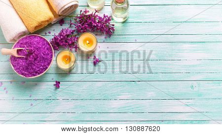Spa setting. Sea salt in bowl bottles with aroma oil towels and candles on turquoise wooden background. Selective focus. Place for text. Flat lay. Toned image.