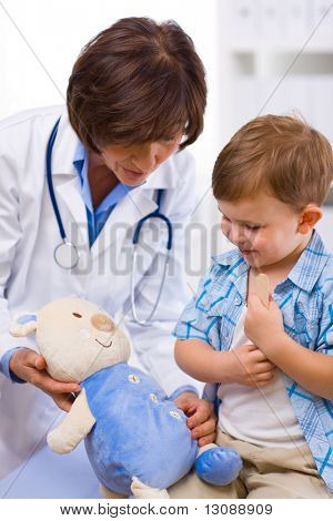 Senior female doctor and happy child examining teddy bear.