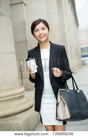 Businesswoman holding a coffee cup and walking at street