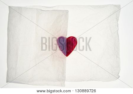 Heart shaped object partially covered by packaging tissue