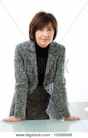 Senior geschäftsfrau stützte sich auf Glasschreibtisch, lächelnd.