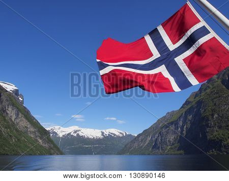 Geiranger fjord with flag of Norway Cruise ferry sunny day