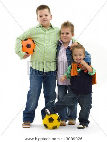 Young boys wearing trendy jeans clothes posing togethers with football, on isolated white background.