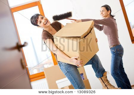 Young women lifting up cardboard box and having fun, while moving to new home.