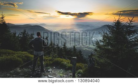 Man standing and looking to nice sunset on czech mountains Beskydy