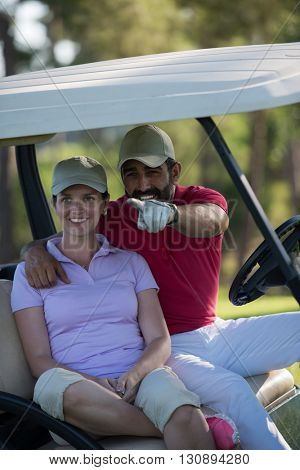 couple in buggy cart on golf course