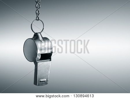 Hanging metal whistle closeup photo. Gray background