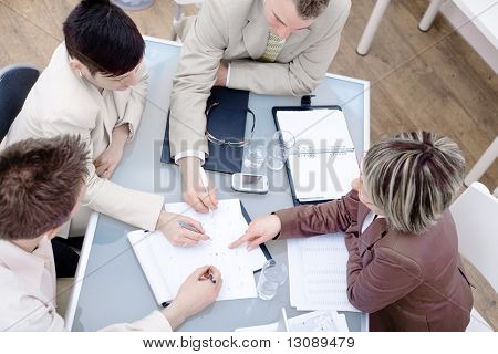 High-angle view of businesspeople having a meeting at office, sitting around the desk and talking.