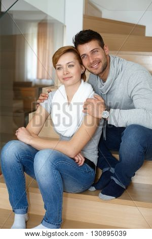 Young loving couple sitting at home in stairway, smiling, looking away heads together.