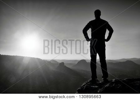 Silhouette Of Young Confident And Powerful Man Standing With Hands On Hips, Morning Or Late Day Sun