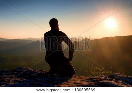 Sportsmann Hiker In Black Sportswear Sit On Mountain Top And Take A Rest. Tourist  Watch Down To Mor