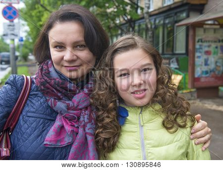 Mother (middle-aged woman) and her daughter, teenager on the street.