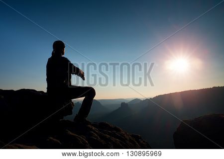 Young Man In Black Sportswear Is Sitting On Cliff And Looking To Misty Valley Bellow