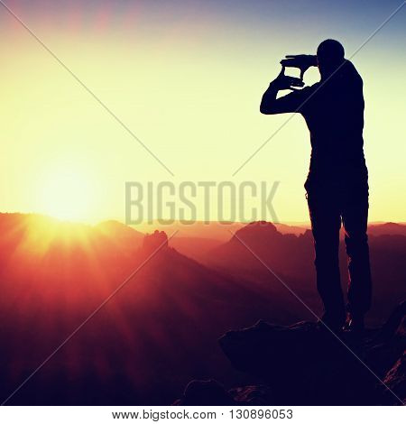 Tourist Make Frame With Palms And Fingers On Both Hands. Hiker On Rocky Cliff, Daybreak In Rocky Mou