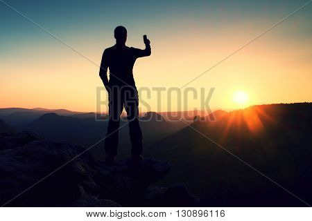 Selfie Mania. Tall Man Hiker Is Taking Selfie Photo By Smart Phone On Peak Of Mountain At Sunrise.
