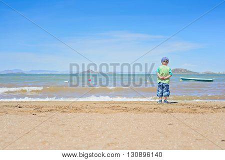 Small boy standing on the beach near Mar Menor sea, Spain